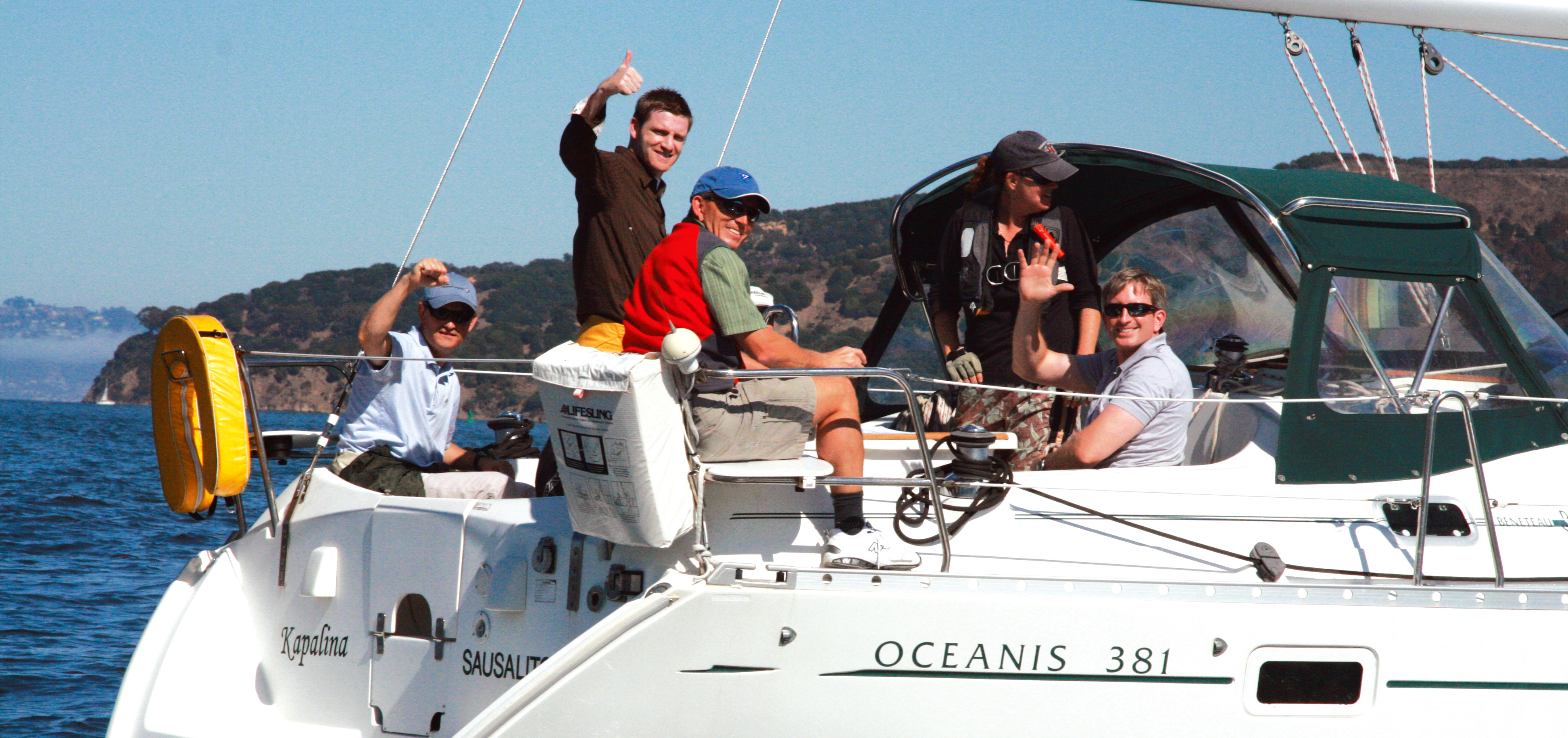 A group of sailors enjoy a hosted sail with thumbs up