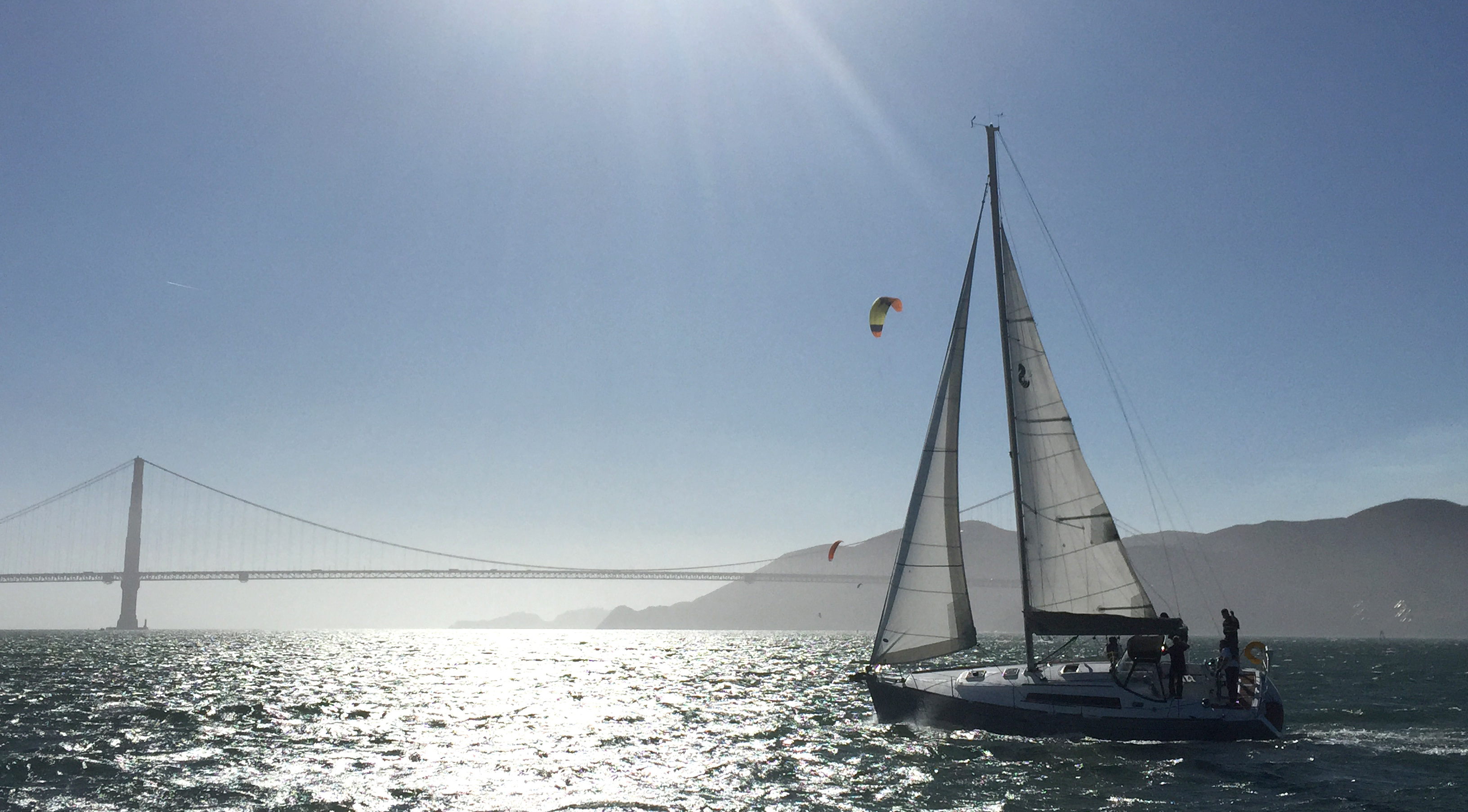 Modern Sailing's Auriah sailing with the Golden Gate Bridge and Kite Boarder in the back ground.