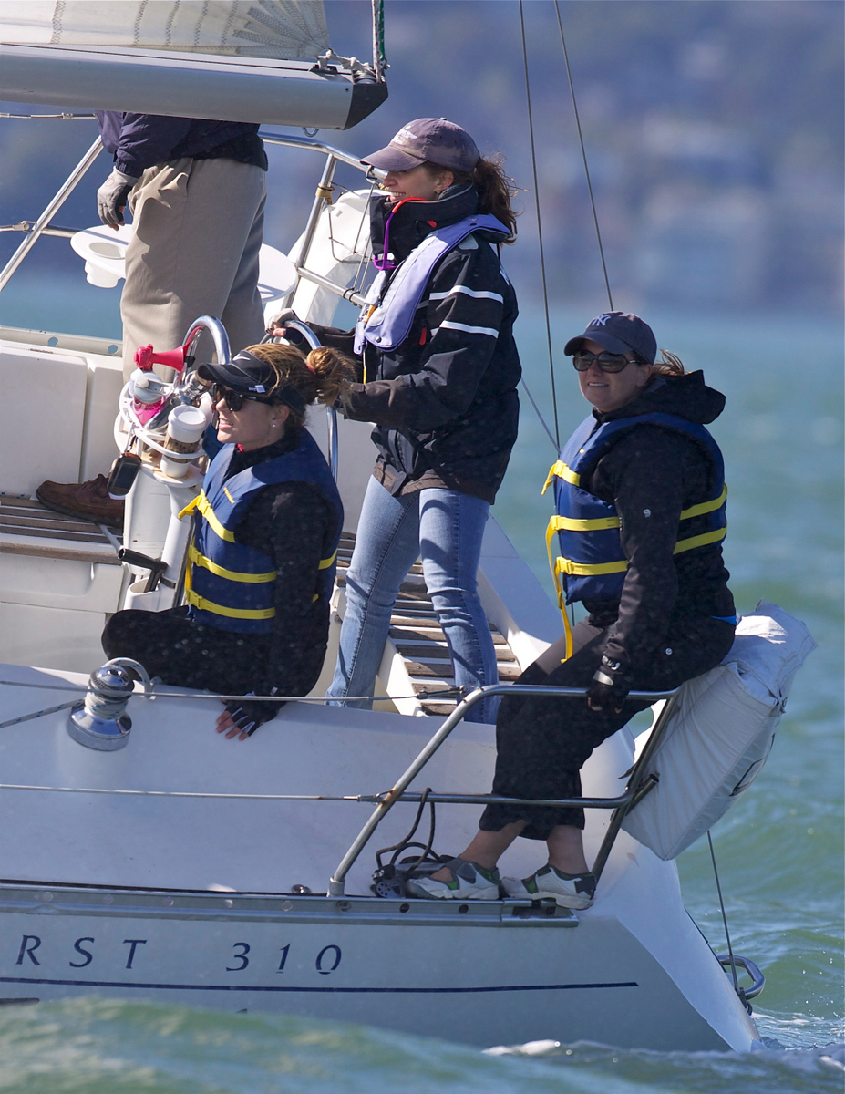 The Beginning Race Clinic practices during a regatta on San Francisco Bay. This photo is of the stern of the boat with three team members concentrating on their jobs.