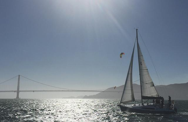 Sailing across San Francisco Bay with the Golden Gate Bridge in the background, student practice skills learned in Basic Keelboat (ASA 101) and Basic Coastal Cruising (ASA 103) 5-day Combination Course at Modern Sailing School and Club
